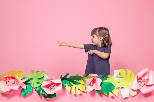 Portret van een klein meisje op een zomer roze achtergrond Gratis Foto