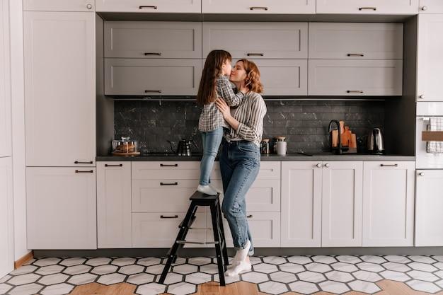 Portret van een klein meisje staat op trappen en knuffels moeder in de keuken. Gratis Foto