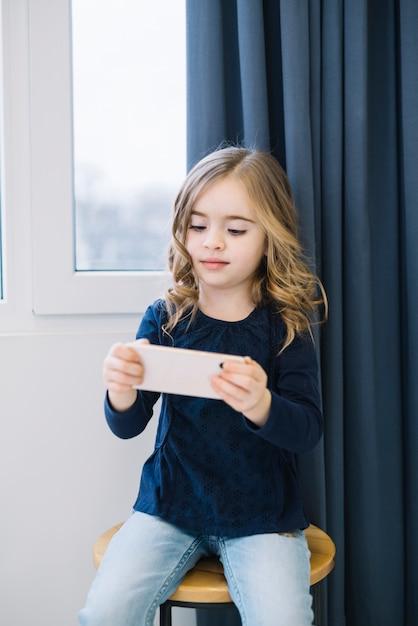 Portret van een klein meisje, zittend op een stoel kijken naar slimme telefoon Gratis Foto