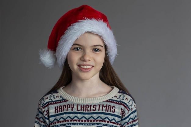 Portret van een klein mooi glimlachend meisje in een nieuwjaarstrui en reclameconcept van de kerstmuts Premium Foto