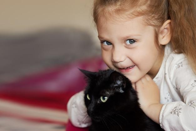 Portret van een klein schattig kind meisje dat een zwarte kat knuffelt met tederheid en liefde en glimlacht van geluk Premium Foto
