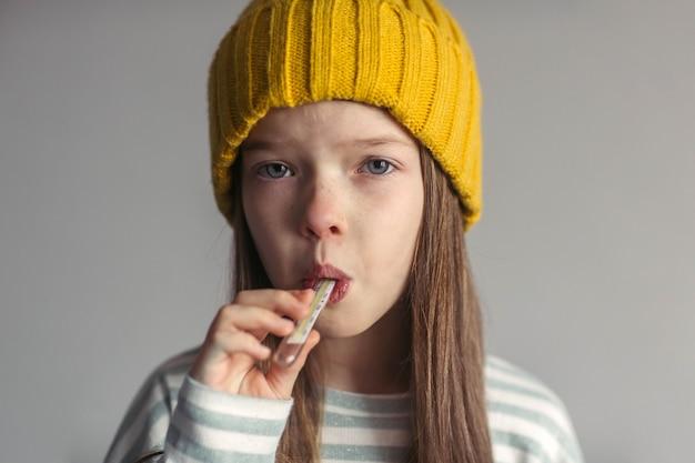 Portret van een klein verdrietig ongelukkig meisje in een hoed die lijdt aan het griepvirus, loopneus en hoofdpijn meet de temperatuur met een thermometer Premium Foto
