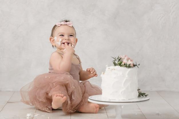 Portret van een klein vrolijk feestvarken met de eerste cake. de eerste cake eten. smash cake. Premium Foto