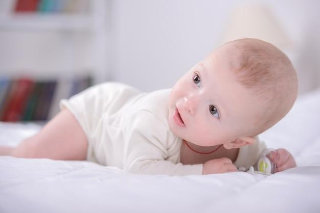 Portret van een kleine baby die op bed speelt. Premium Foto