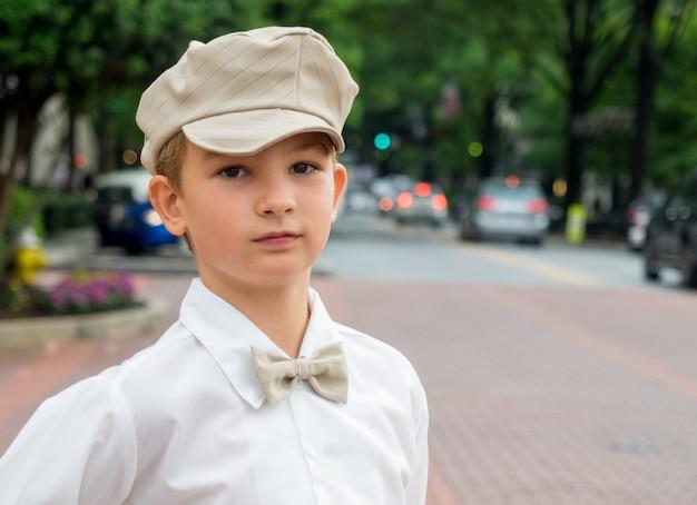 Portret van een kleine jongen met een vlinderdas en een hoed in het park met een onscherpe achtergrond Gratis Foto