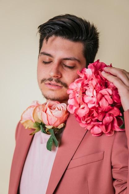 Portret van een knappe jongen met dichte ogen. knappe jongeman met bloemen om zijn nek en naast zijn gezicht, gekleed in een roze pak Premium Foto