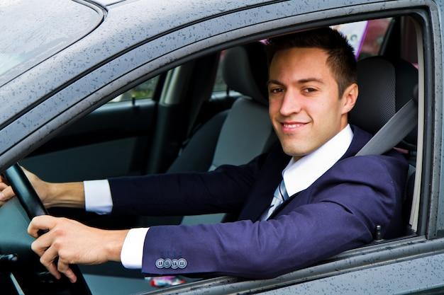 Portret van een knappe kerel die zijn auto drijft Premium Foto