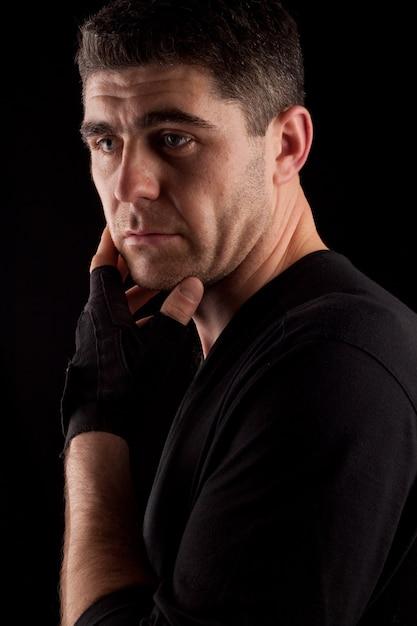 Portret van een knappe man van atletische build in een zwart sportshirt en sporthandschoenen op een zwarte ondergrond Premium Foto