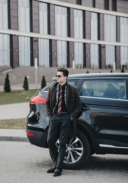 Portret van een knappe zakenman die zich dichtbij de auto buiten dichtbij modern gebouw bevindt Premium Foto