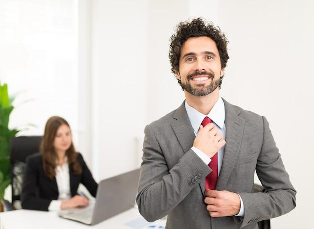 Portret van een knappe zakenman die zijn band aanpast Premium Foto