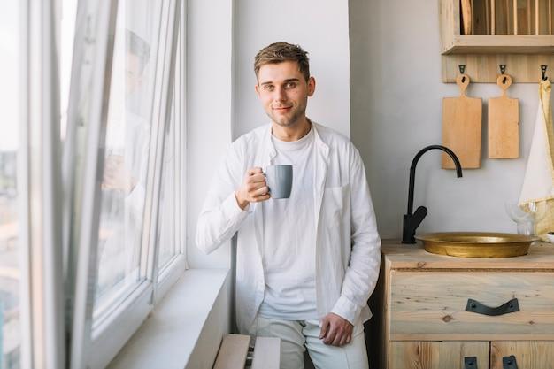Portret van een kop van de jonge mensenholding van koffie die zich in keuken bevinden Gratis Foto