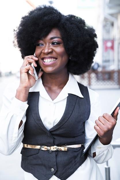 Portret van een lachende jonge afrikaanse zakenvrouw klembord in de hand te houden praten op mobiele telefoon Gratis Foto