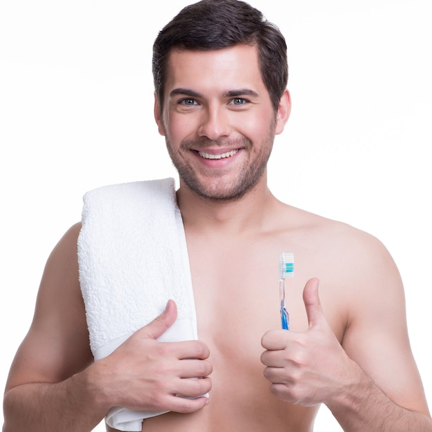 Portret van een lachende jonge man met een tandenborstel - geïsoleerd op wit. Gratis Foto