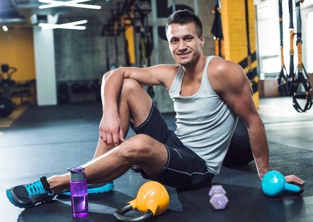Portret van een lachende jonge man zittend op de vloer in de buurt van oefeningsapparatuur in de sportschool Gratis Foto