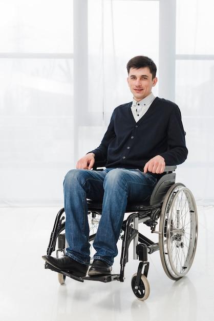 Portret van een lachende jonge man zittend op rolstoel camera kijken Gratis Foto