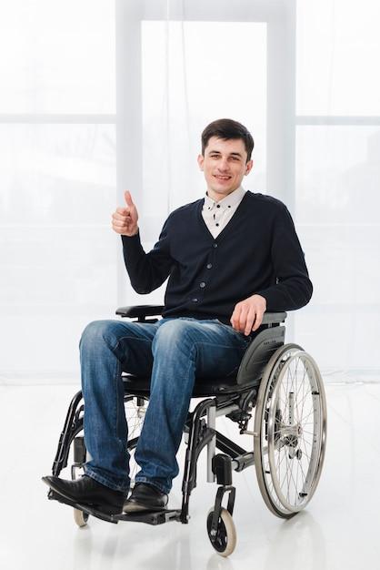 Portret van een lachende jonge man zittend op rolstoel met duim omhoog teken Gratis Foto