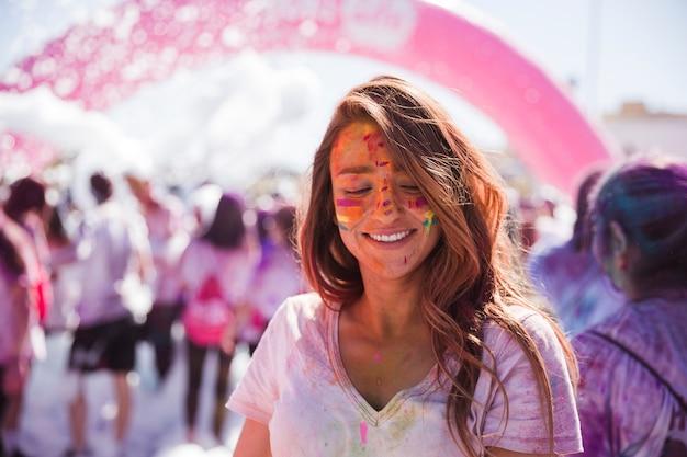 Portret van een lachende jonge vrouw met holi kleur gezicht Gratis Foto