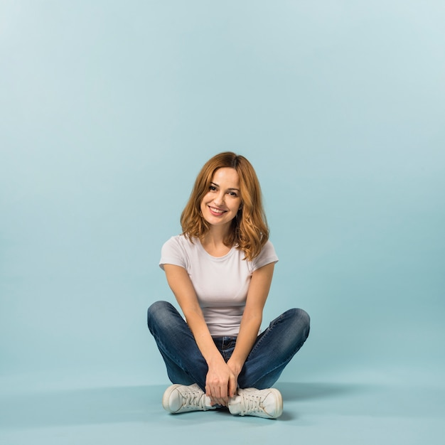 Portret van een lachende jonge vrouw zittend op de vloer tegen een blauwe achtergrond Gratis Foto