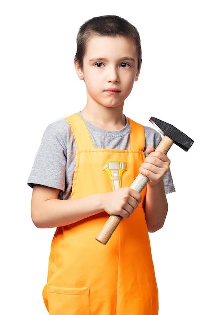 Portret van een lachende jongen timmerman in oranje werk overall poseren, met een hamer in zijn handen plezier op een witte geïsoleerde achtergrond. kinderkostuum voor de feestdagen Premium Foto