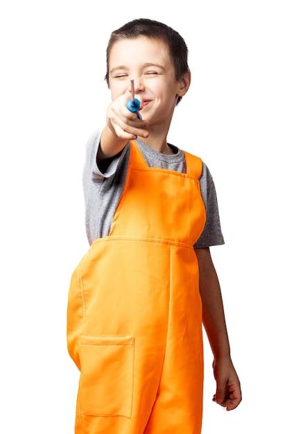 Portret van een lachende jongen timmerman in oranje werk overall, poseren, met een schroevendraaier op een witte geïsoleerde achtergrond. Premium Foto