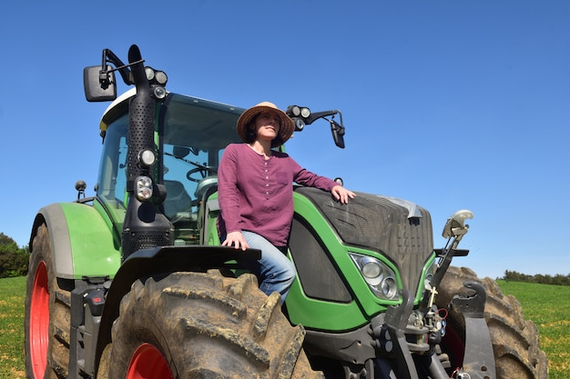 Portret van een landbouwersvrouw en een tractor op het gebied Premium Foto