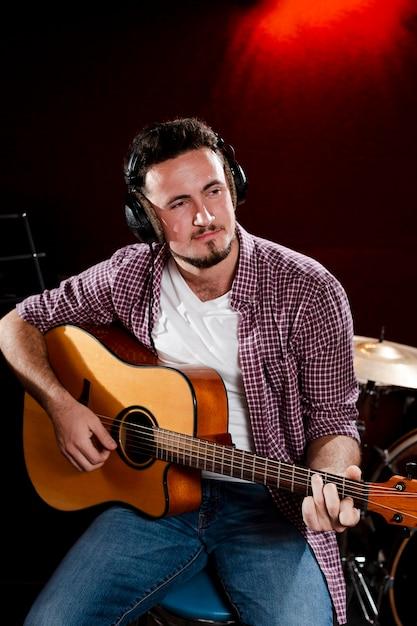 Portret van een man die gitaar speelt en een koptelefoon draagt Gratis Foto