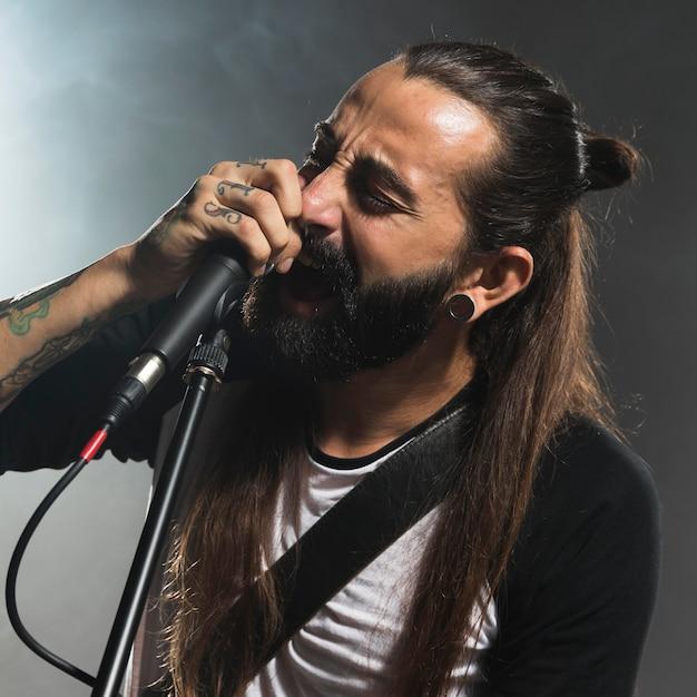 Portret van een man die op het podium zingt Gratis Foto