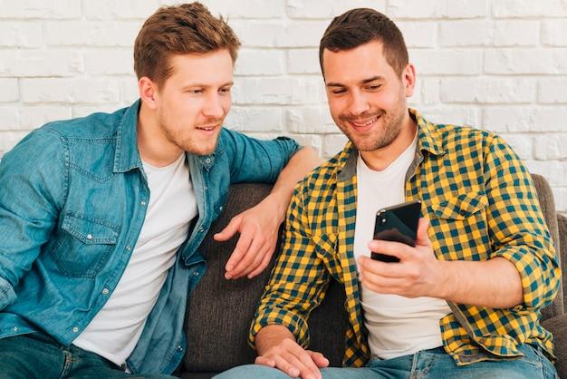 Portret van een man iets te tonen aan zijn vriend op smartphone Gratis Foto