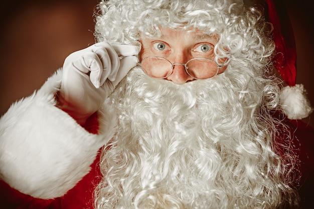 Portret van een man in kerstman-kostuum - met een luxe witte baard, kerstmuts en een rood kostuum op een rode studioachtergrond. het gezicht van dichtbij Gratis Foto