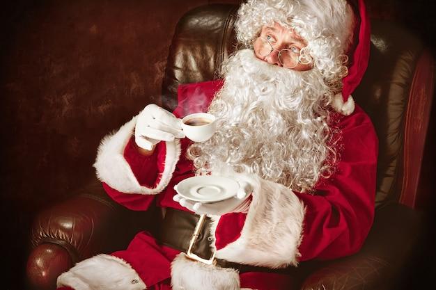 Portret van een man in kerstman kostuum - met een luxe witte baard, kerstmuts en een rood kostuum op rode studio achtergrond zittend in een stoel met een kopje koffie Gratis Foto