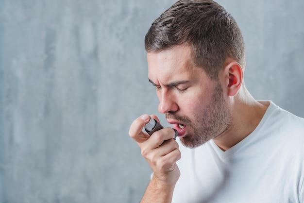 Portret van een man met gesloten ogen met behulp van astma-inhalator Gratis Foto
