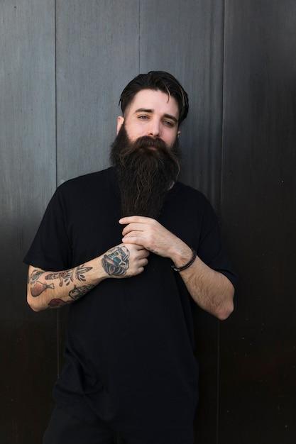 Portret van een man met lange, bebaarde man tegen zwarte houten muur Gratis Foto