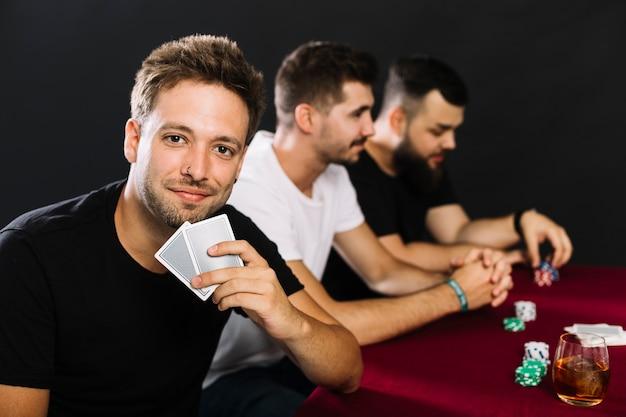 Portret van een man met speelkaarten in casino Gratis Foto