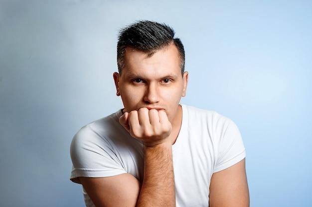 Portret van een man op een lichte achtergrond, verveeld, emotie van verveling. Premium Foto