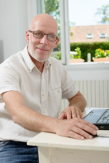 Portret van een man van middelbare leeftijd met laptop Premium Foto