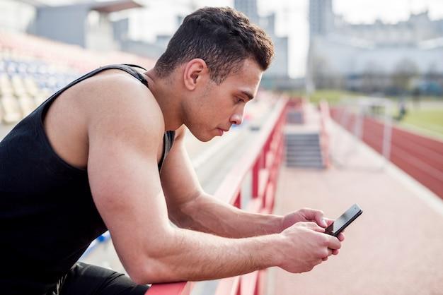 Portret van een mannelijke atleet die mobiele telefoon met behulp van bij stadion Gratis Foto