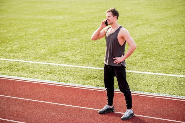 Portret van een mannelijke atleet die zich op rasspoor bevindt dat op slimme telefoon spreekt Gratis Foto