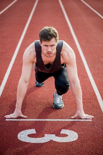 Portret van een mannelijke sprinter klaar voor race op circuit Gratis Foto