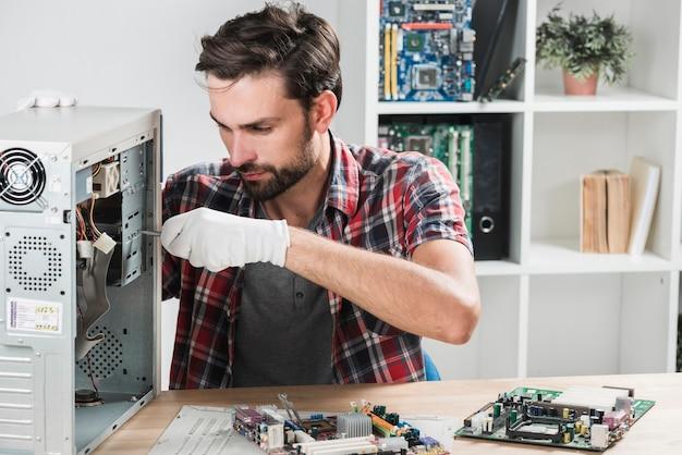 Portret van een mannelijke technicus die computer herstelt Gratis Foto