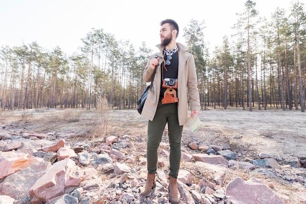 Portret van een mannelijke wandelaar die een generieke kaart in het bos houdt dat weg eruit ziet Gratis Foto