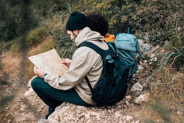 Portret van een mannelijke wandelaar die kaartzitting bekijken met zijn vriend Gratis Foto