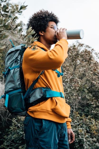 Portret van een mannelijke wandelaar die met zijn rugzak het water van fles drinkt Gratis Foto