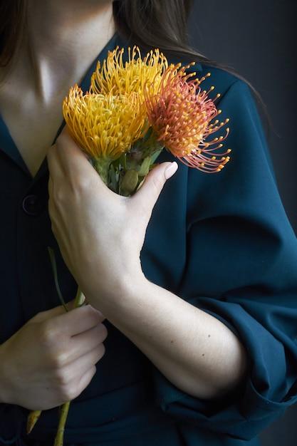 Portret van een meisje dat drie gele en oranje proteas houdt Premium Foto