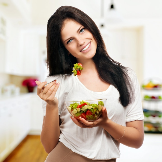 Portret van een meisje dat positief kijkt en een schreeuwt met salade houdt Premium Foto