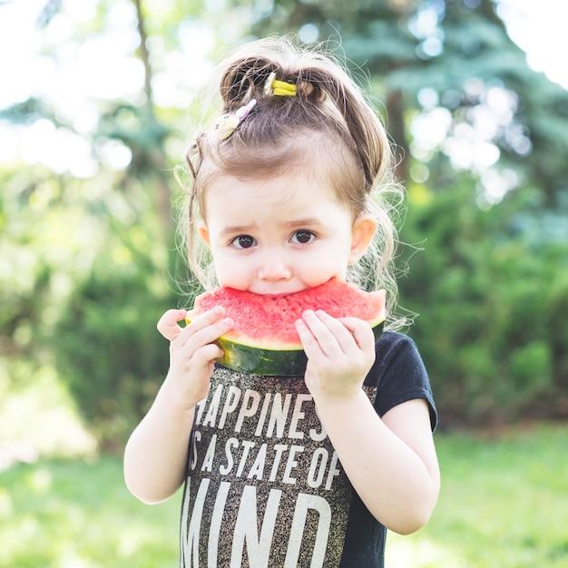 Portret van een meisje dat verse watermeloenplak eet Gratis Foto