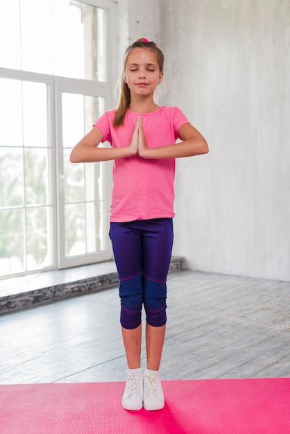 Portret van een meisje dat zich op de meditatie van de oefeningsmat bevindt Gratis Foto