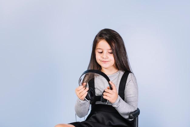 Portret van een meisje die hoofdtelefoon tegen blauwe achtergrond bekijken Gratis Foto