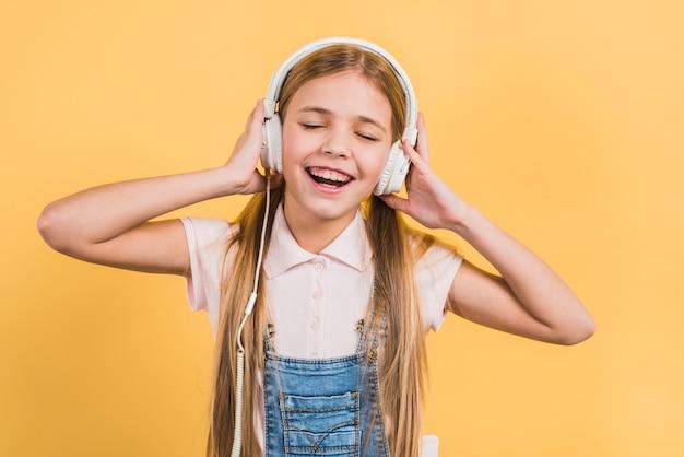 Portret van een meisje die van de muziek op hoofdtelefoon genieten die zich tegen gele achtergrond bevinden Gratis Foto