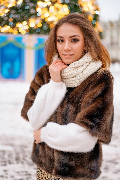 Portret van een meisje in een bontjas op de achtergrond van een kerstboom. Premium Foto