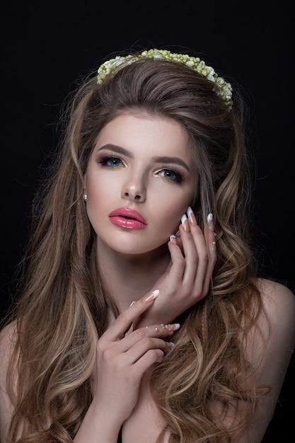 Portret van een meisjesclose-up met aardige haarstijl, manicure en samenstelling. de kroon van bloemen siert haar hoofd Premium Foto